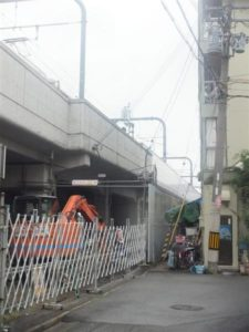 車掌が飛び降りた高架。手前にある金属製門扉の内側に落下した=大阪府東大阪市
